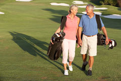 Senior Couple Walking Along Golf Course Stock Photo