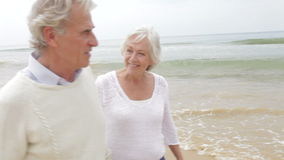 Senior Couple Walking Along Misty Beach. Senior couple walking along beach talking to one another.Shot on Canon 5D Mk2 at at a frame rate of 25 fps stock video footage