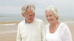 Senior Couple Walking Along Misty Beach stock footage
