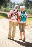 Senior couple walking along reading a map Stock Photos
