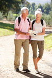 Senior couple walking along reading map stock photo