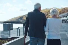 Senior couple walking along riverwalk Stock Photo
