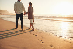 Senior couple walking along the sea shore. Rear view of a senior couple walking along the sea shore. Mature men and women together strolling on the sea shore at Royalty Free Stock Photography