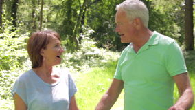 Senior Couple Walking Along Summer Woodland Path Together. Camera tracks happy senior couple as they walk along leafy summer woodland path smiling and talking stock video footage