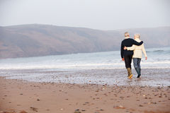 Senior Couple Walking Along Winter Beach Royalty Free Stock Photo