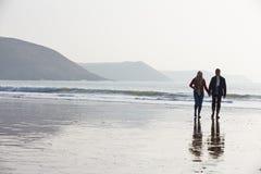 Senior Couple Walking Along Winter Beach Royalty Free Stock Photo