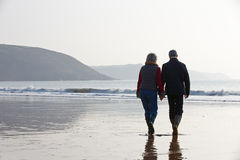 Senior Couple Walking Along Winter Beach Royalty Free Stock Images