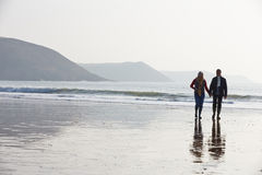 Senior Couple Walking Along Winter Beach Royalty Free Stock Image