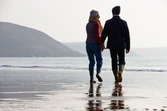 Senior Couple Walking Along Winter Beach Stock Images