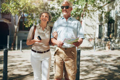 Senior couple walking around the city holding a map Stock Photos