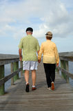 Senior couple walking back view. A back view of a senior couple outdoors holding hands walking on a boardwalk stock photos