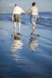 Senior Couple Walking On Beach Stock Image