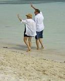 Senior couple walking beach. Attractive senior couple waving while walking on the beach Stock Images