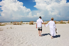 Senior couple walking beach. Back view of an old couple walking on the sandy beach royalty free stock images