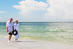 Senior couple walking on beach. An elderly couple walking hand in hand at the beach royalty free stock photography