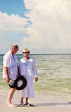 Senior couple walking beach. An elderly couple walking hand in hand at the beach stock photo