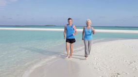 Senior Couple Walking On Beautiful Beach. Camera tracks senior couple as they walk along beautiful beach looking happy.Shot on Canon 5d Mk2 with a frame rate of stock video