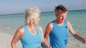 Senior Couple Walking On Beautiful Beach