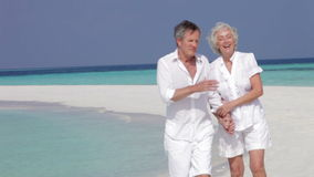 Senior Couple Walking On Beautiful Beach stock footage