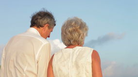 Senior Couple Walking On Beautiful Beach. Rear view of senior couple as they walk away from camera.Shot on Canon 5d Mk2 with a frame rate of 30fps stock video footage