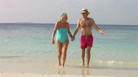 Senior Couple Walking On Beautiful Beach. Senior couple walk out of sea and past camera position.Shot on Canon 5d Mk2 with a frame rate of 30fps stock video