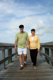 Senior couple walking on boardwalk. A senior couple outdoors holding hands walking on a boardwalk royalty free stock images