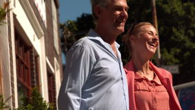Senior couple walking in the city on a sunny day stock footage
