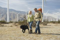 Senior Couple Walking With Dog Near Wind Farm. Senior couple walking with dog on landscape near wind farm Royalty Free Stock Image