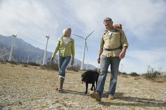 Senior Couple Walking With Dog Near Wind Farm. Senior couple walking with dog on landscape near wind farm Royalty Free Stock Images