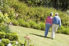 Senior couple walking in garden stock photography