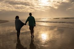 Senior couple walking hand in hand on the beach. Rear view of active senior couple walking hand in hand on the beach royalty free stock images