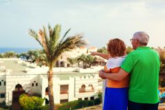 Senior couple walking on hotel territory admiring the sea view. People enjoying vacation. Traveling concept stock image