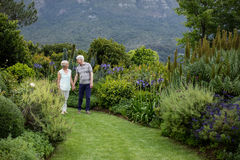 Senior couple walking in lawn stock photography