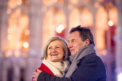 Senior couple walking in night city. Winter, Historical building Stock Images