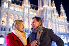 Senior couple walking in night city. Winter, Historical building Royalty Free Stock Photography