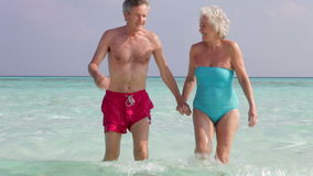 Senior Couple Walking Out Of Tropical Sea stock video footage