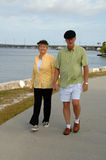 Senior couple walking in park. A senior couple outdoors holding hands walking in a park by the harbor Royalty Free Stock Photo