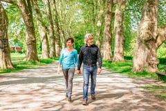 Senior Couple Walking Through A Park, Tuebingen, Germany. Senior couple walking through a park, Neckarinsel, Tuebingen, Germany Royalty Free Stock Images