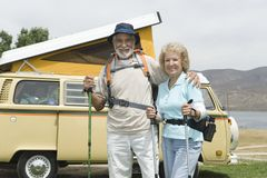 Senior Couple With Walking Poles And Campervan. Portrait of a happy senior couple with walking poles and campervan in the background Stock Photo