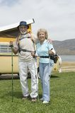 Senior Couple With Walking Poles And Campervan. Portrait of a happy senior couple with walking poles and campervan in the background Stock Photos