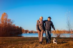 Senior couple walking pug dog in autumn park by river. Happy man and woman enjoying time with pet. royalty free stock photography
