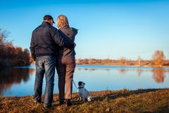 Senior couple walking pug dog in autumn park by river. Happy man and woman enjoying time with pet. royalty free stock images