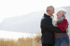 Senior Couple Walking Through Sand Dunes On Winter Beach Royalty Free Stock Photography