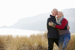 Senior Couple Walking Through Sand Dunes On Winter Beach Royalty Free Stock Images