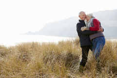 Senior Couple Walking Through Sand Dunes On Winter Beach Stock Photography