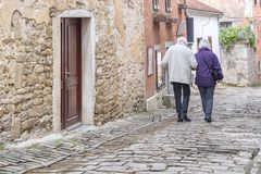 A senior couple walking on the streets of an ancient city. royalty free stock photography