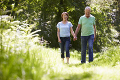 Senior Couple Walking In Summer Countryside Stock Photo