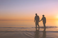 Senior couple walking at sunset Stock Images