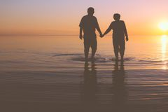 Senior couple walking at sunset Stock Image