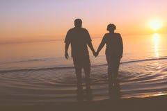 Senior couple walking at sunset Royalty Free Stock Images
